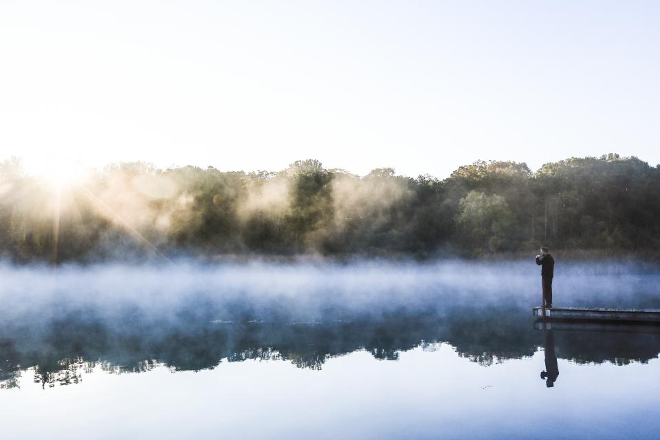 lake water fog foggy mist reflection dock guy man people nature landscape trees sunshine sky