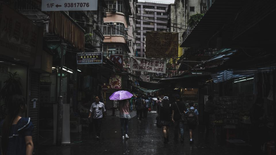 street road architecture houses establishment shops people posts asian men women bricks umbrella