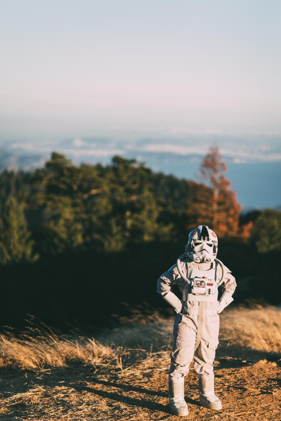 people man alone costume astronaut science sunny day travel grass highland blur sky clouds