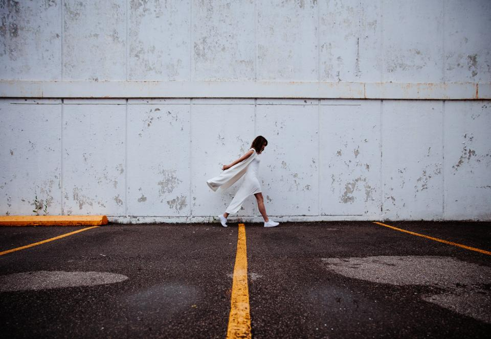 building wall people white dress girl woman female walking alone sad outdoors asphalt road