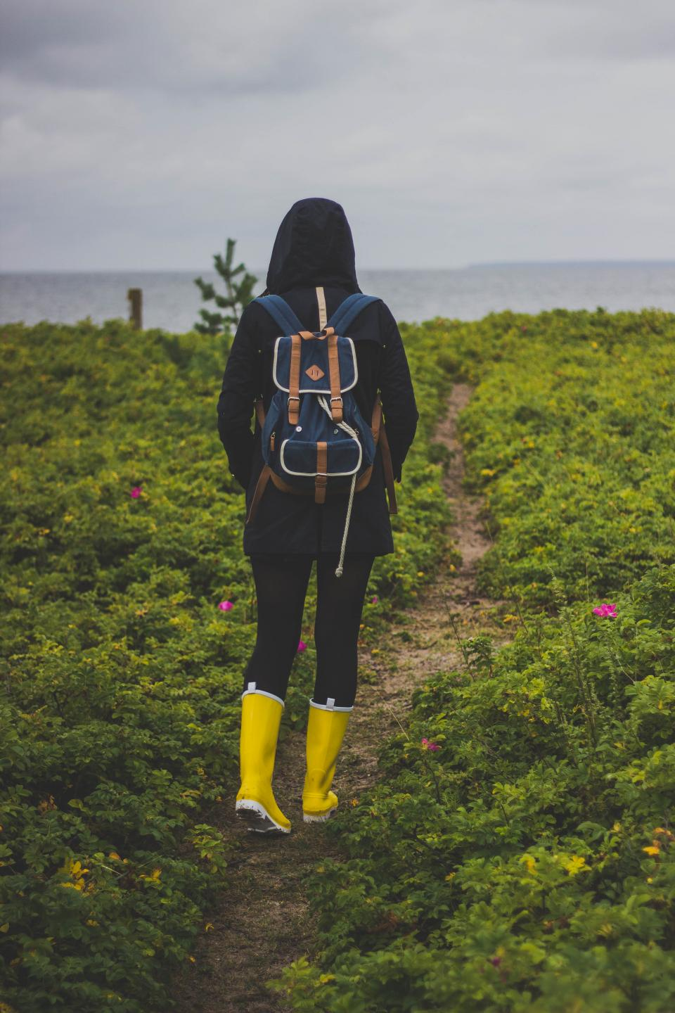green grass path outdoor field people walking girl woman nature travel adventure back hoodie jacket yellow boots bag sea ocean water sky cloud horizon