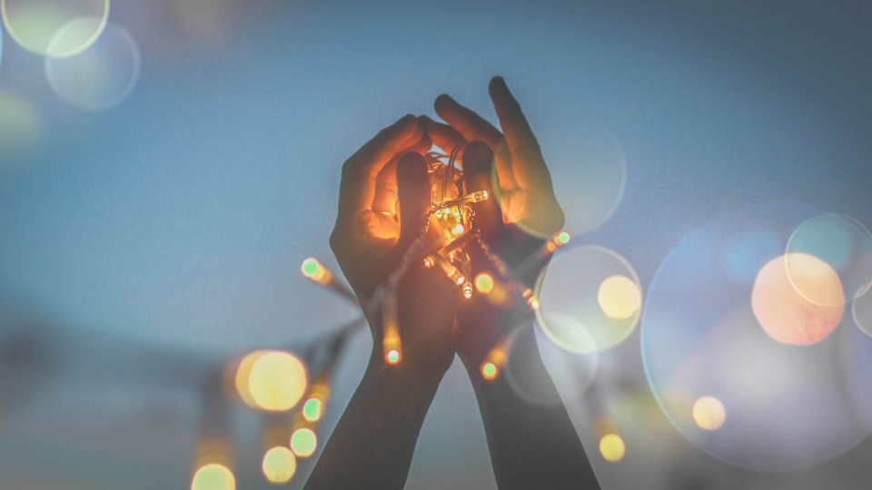 woman holding light fairy lights led bokeh hands sky night dusk people