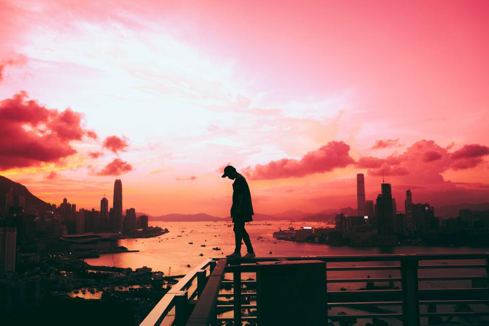 architecture building infrastructure people man alone skyline sunset clouds sky city urban view sea ocean water silhouette