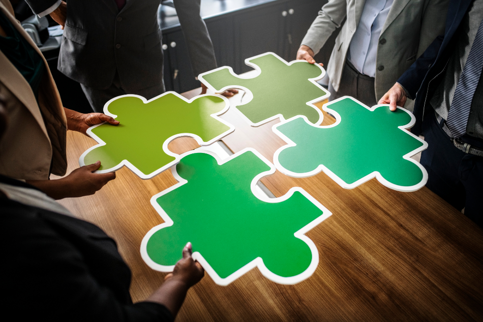 business collaboration colorful communication connected connecting connection cooperation environment environmental conservation green green business group holding inspiration jigsaw join joining laying man meeting meeting room mergin
