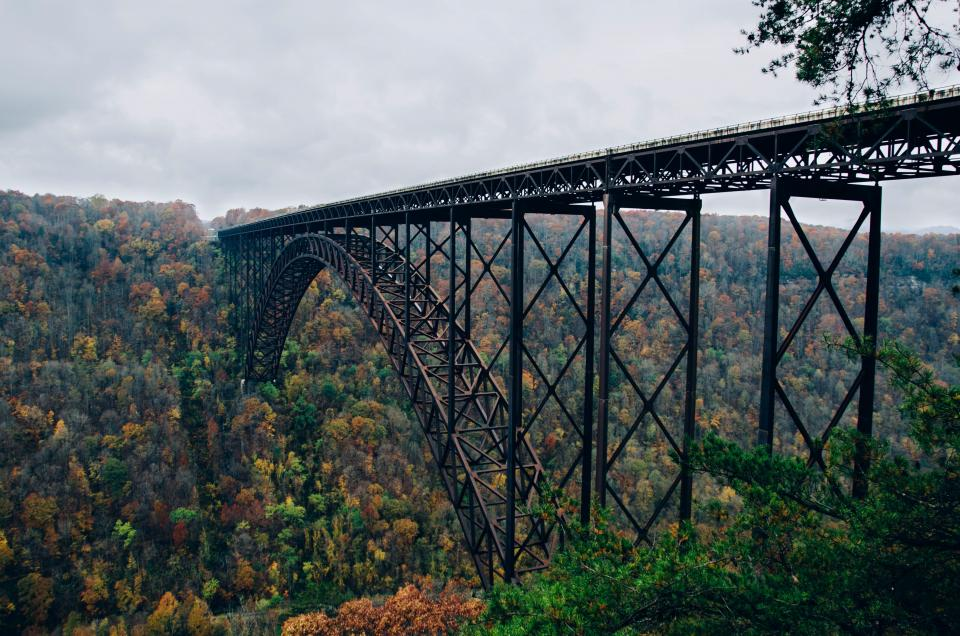 bridge architecture train tracks railroad railway trees fall autumn landscape nature mountains hills forest clouds cloudy outdoors
