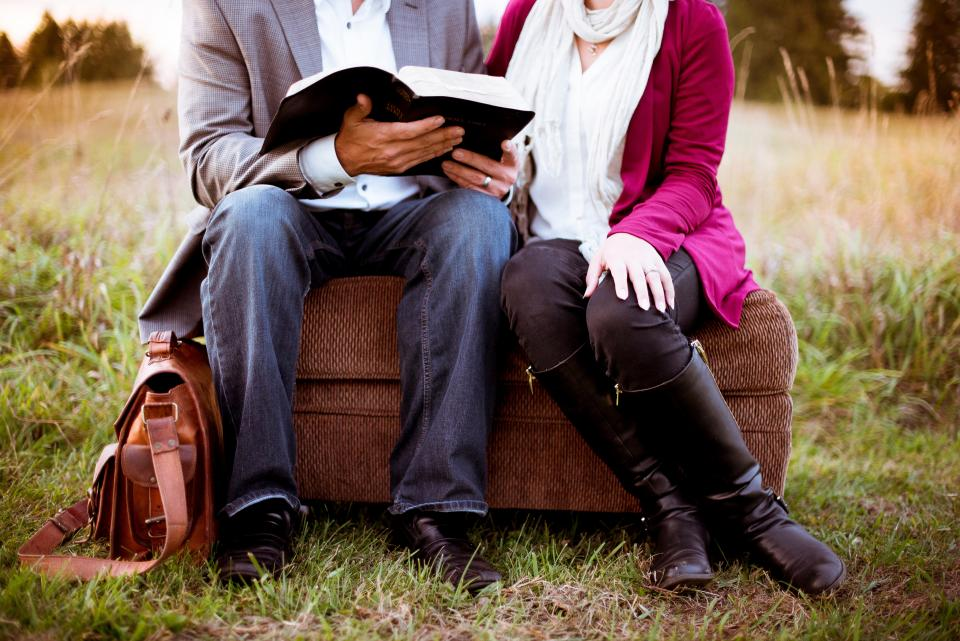 people man woman couple sitting reading book bible bag outside nature green grass