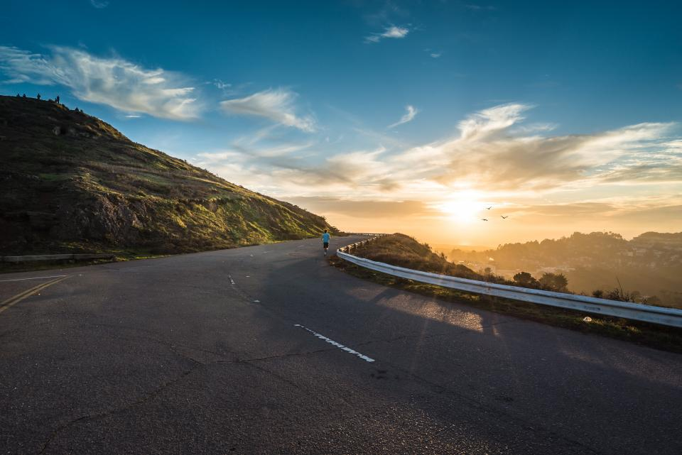road pavement highway sunset sky clouds outdoors landscape nature fitness running runner people guardrail