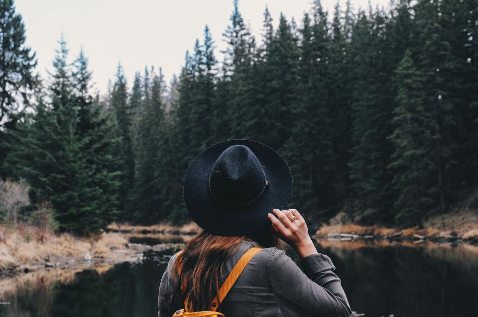 girl woman people hat fashion travel adventure outdoors pine trees forest woods river water hiking trekking journey wanderlust