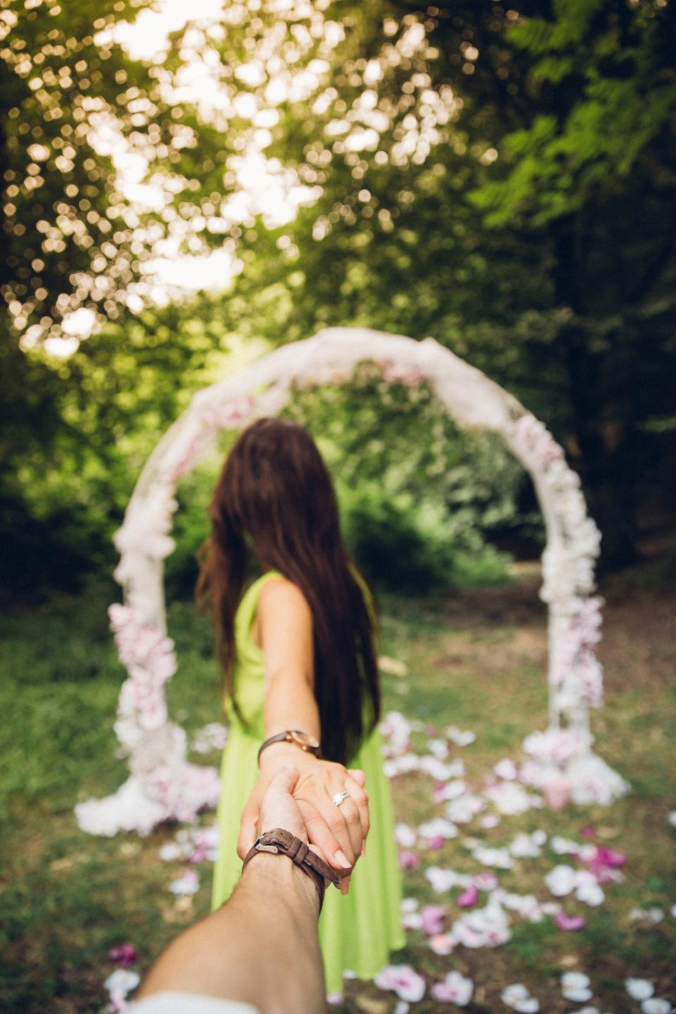 people girl woman holding hands watch ring blur bokeh outdoor green trees plant
