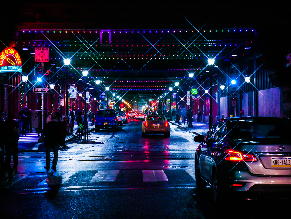 city stree night lights crosswalk cars traffic urban people walking busy neon