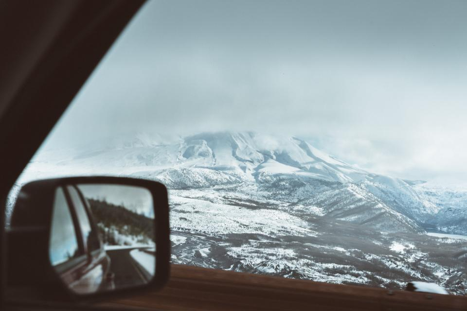 mountain landscape peak summit snow trees pines view aesthetic rocks fog sky clouds view side mirror vehicle
