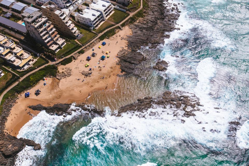 sea ocean water coast rocks beach shore aerial view buildings structure resort cottage vacation travel