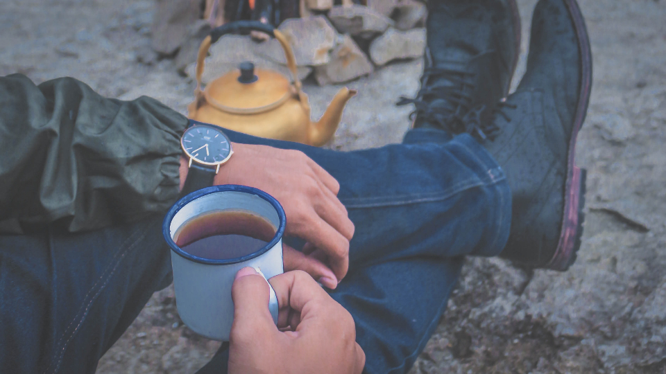 man campfire coffee cup watch analog kettle drink tea fire boots walk hike adventure