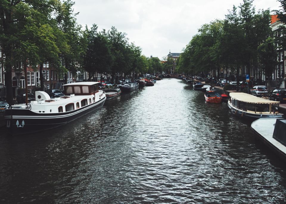 canal water boats trees city town