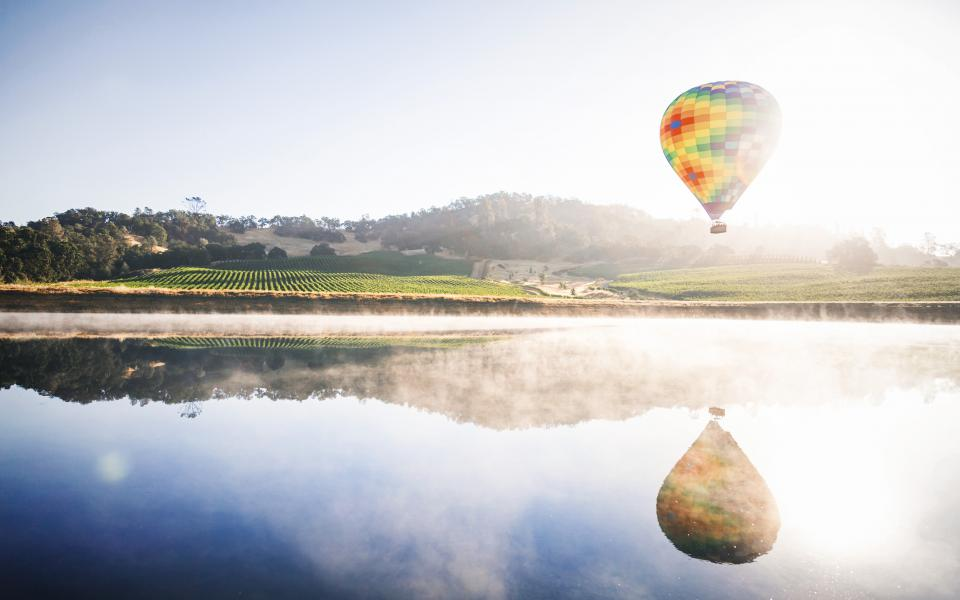 hot air balloon blue sky clouds lake water reflection mountain field outdoor nature view landscape
