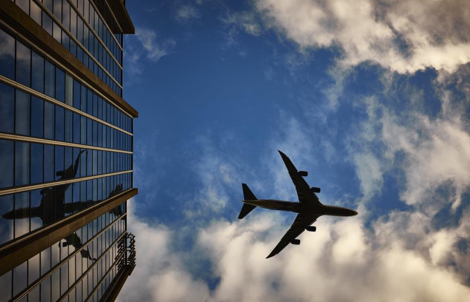 airplane travel transportation trip blue sky clouds shadow building high rise windows reflection city urban