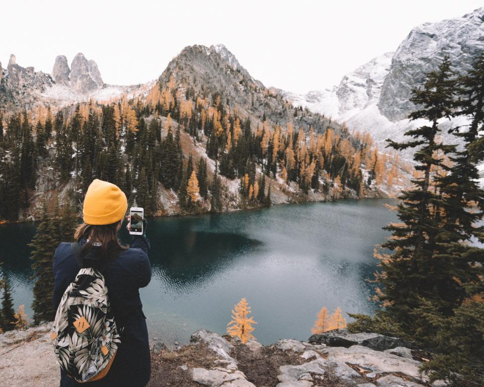 lake water tree plant nature forest reflection mountain valley snow winter cold weather people alone girl beanie bag travel adventure outdoor mobile phone touchscreen selfie camera