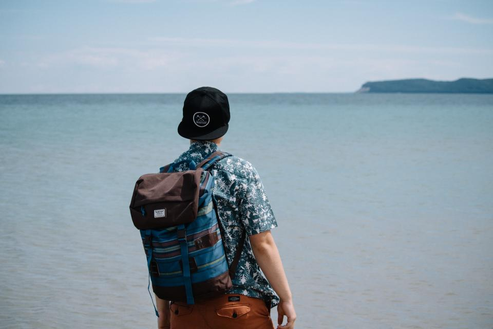 people man alone travel adventure cap ocean sea beach mountain nature herschel back pack bag clouds sky