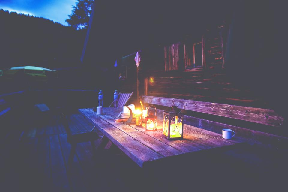 house home residential cabin cottage exterior wood panels pallet lamps candles cups bench chairs view night
