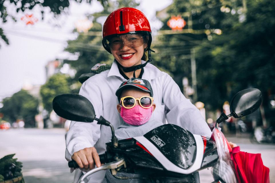 mother son riding motorcycle helmet eyeglasses road street trees bokeh kid child woman boy mask smile happy