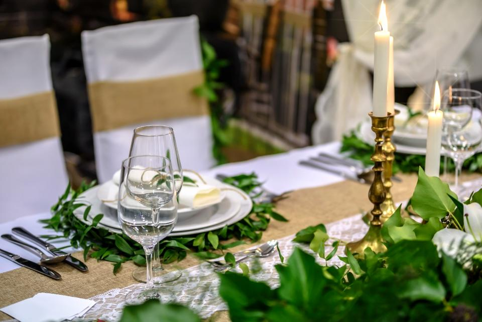 table setup napkin cutlery plate candle dinner date green leaf plant restaurant