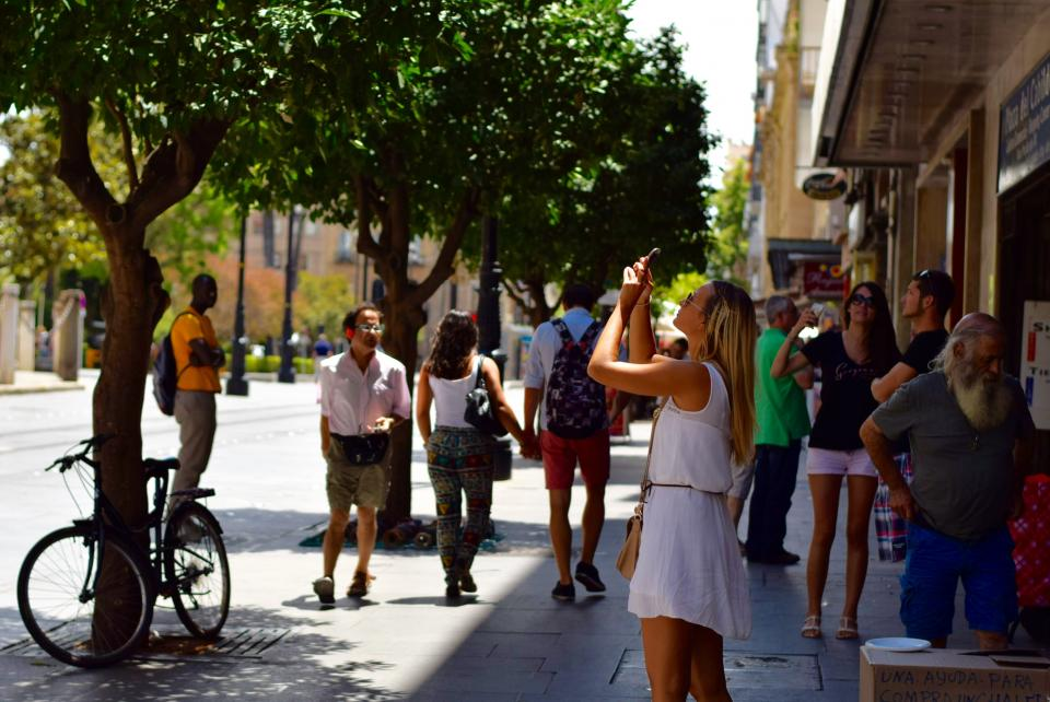 girl picture seville street phone sun people sidewalk city