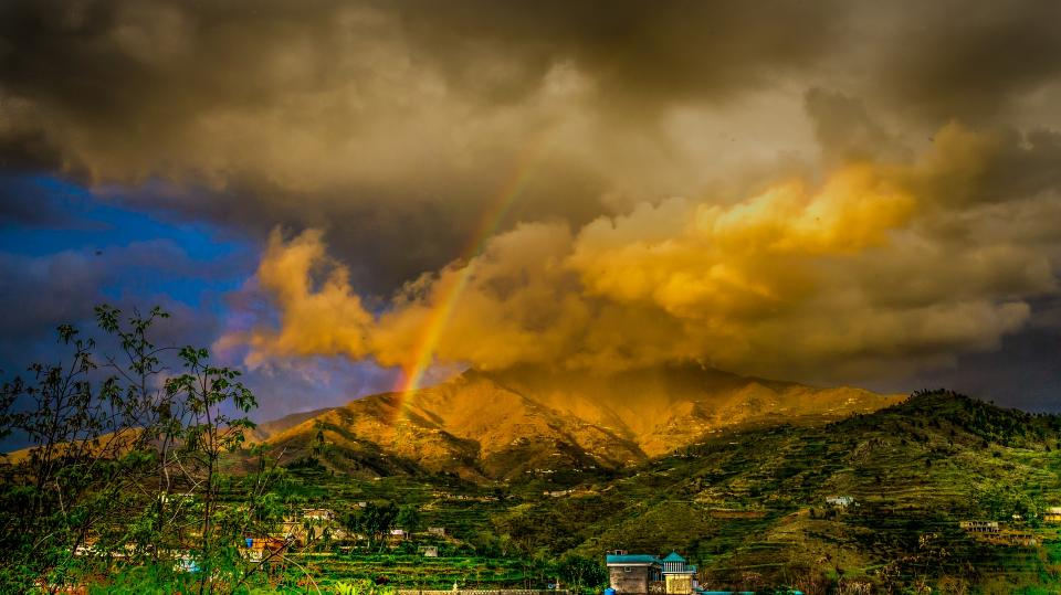landscape dark sky clouds mountain rainbow houses trees grass farm nature