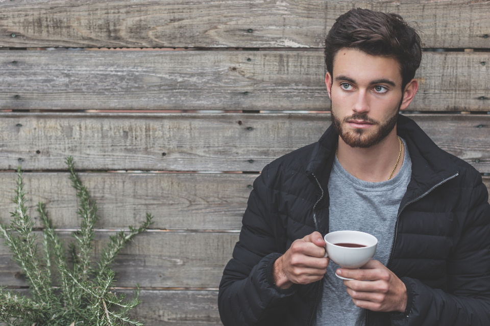 man coffee wood wall plant rustice young people male grey t shirt jacket cup tea drink food beard