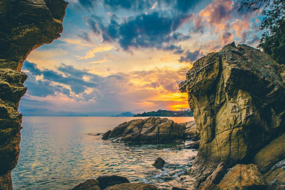 beach shore coast ocean sea horizon sunset dusk sky clouds rocks cliffs boulders landscape nature