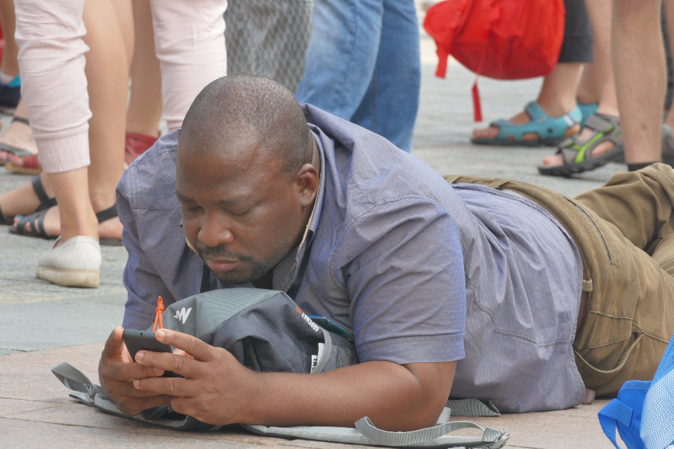 festivity assembly event black negro people color man phone smartphone lie position on the ground