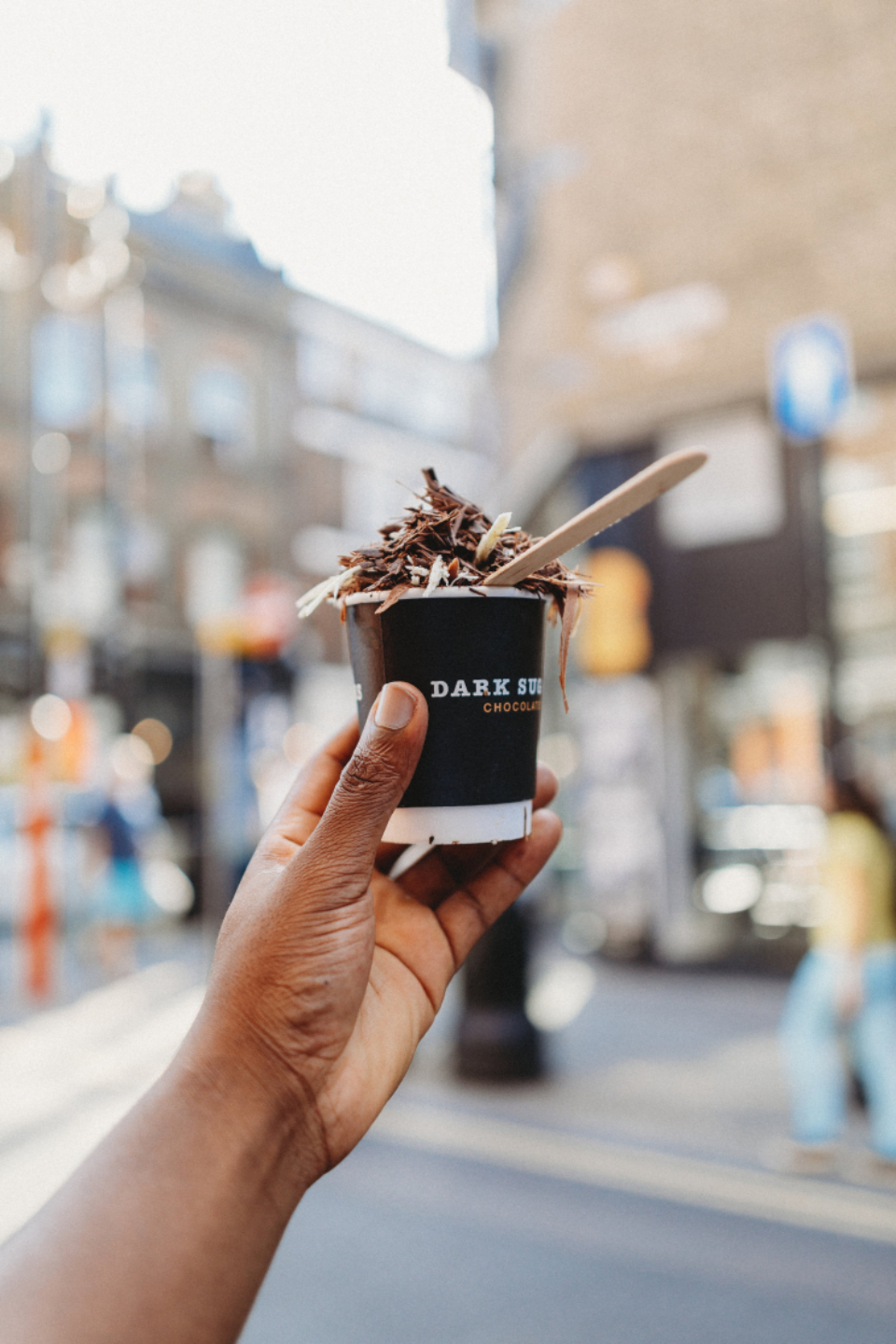 hand holding ice cream food dessert tasty chocolate snack city street nutrition bokeh delicious yummy people