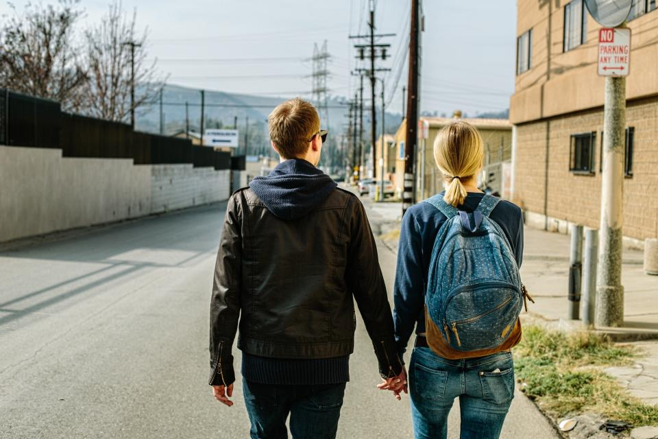 people man woman girl female male guy walking holding hands backpack travel back hoodie jacket building road street sunny day sky