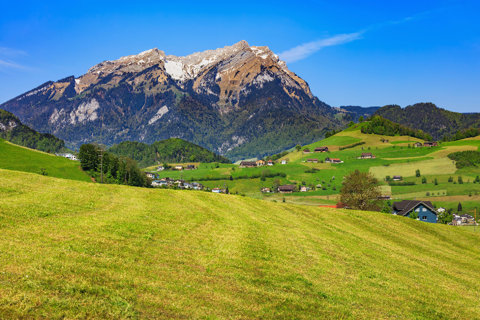 Stanserhorn Pilatus springtime spring meadow grass mown green view countryside agriculture village building house landscape Stans Switzerland Nidwalden sky blue cloud white Swiss hill Alps Swiss Alps mountain nature