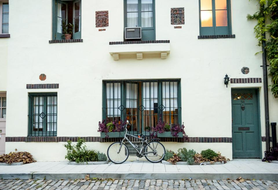 bike bicycle building windows shutters sidewalk street road cobblestone city urban