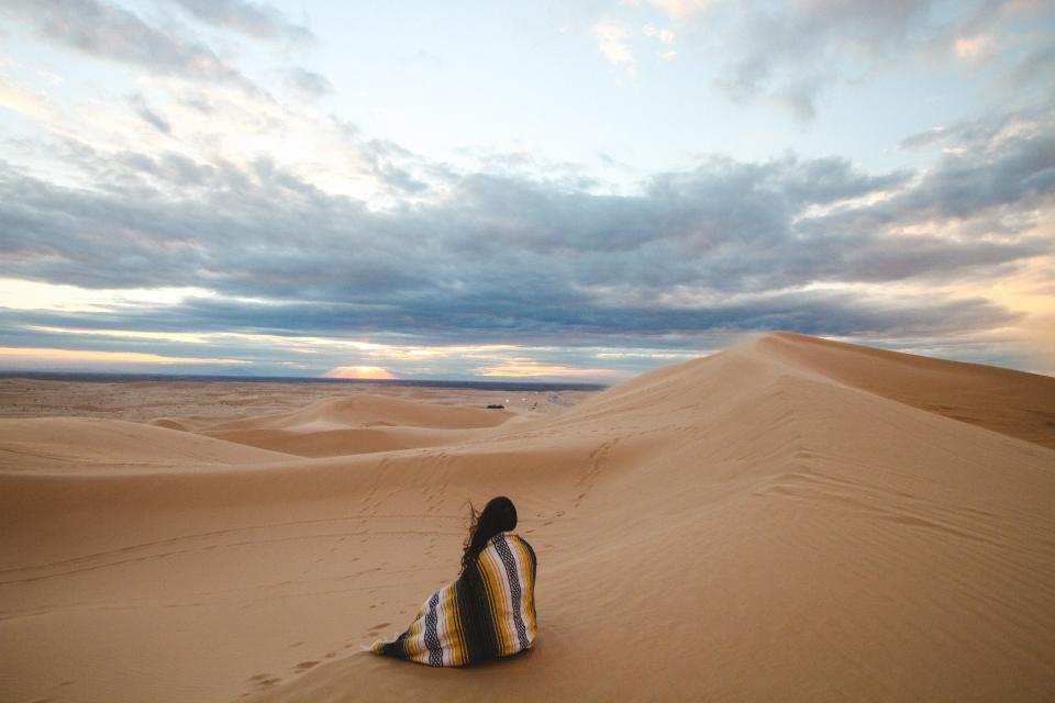 people woman alone travel adventure sand desert clouds sky footsteps nature