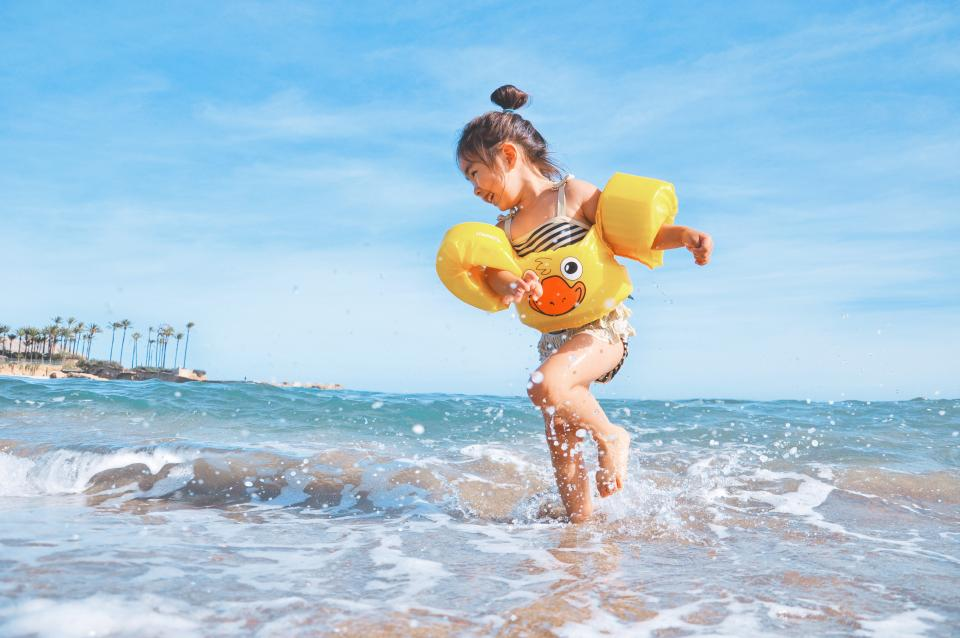 kid child young girl playing fun happy smile smiling laughing beach sand water ocean sea blue sky summer sunshine floaties swimming