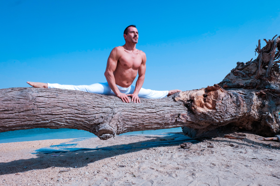 man splits tree yoga beach water sea travel sport health fitness fit muscles strong