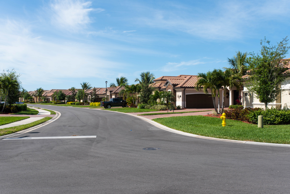 suburban street houses road neighborhood home suburb property america exterior daytime sky trees grass