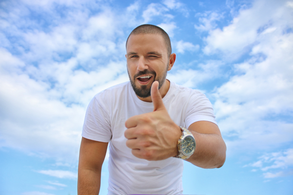 man thumbs up wink smile happy blue sky clouds white t shirt watch