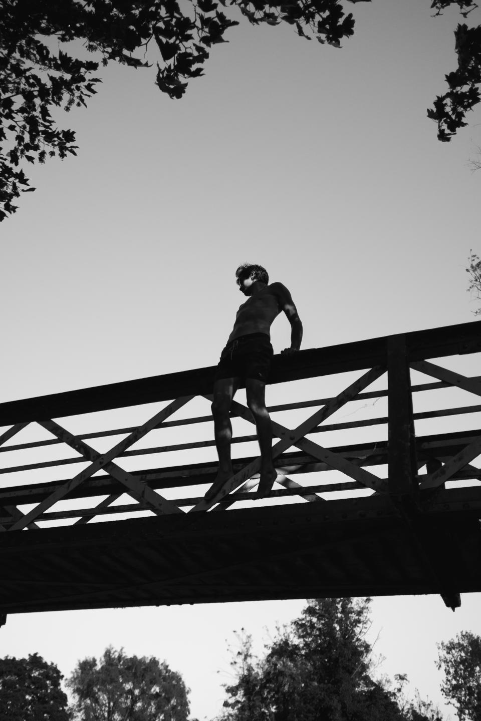 bridge infrastructure trees plants nature outdoor people man alone jump silhouette black and white sky