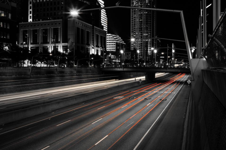 street urban bridge cars lights black and white buildings architecture structure infrastructure road night dark