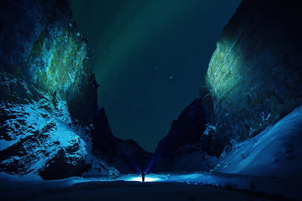 ice cave rocks snow winter flashlights people travel outdoor adventure hill night stars sky