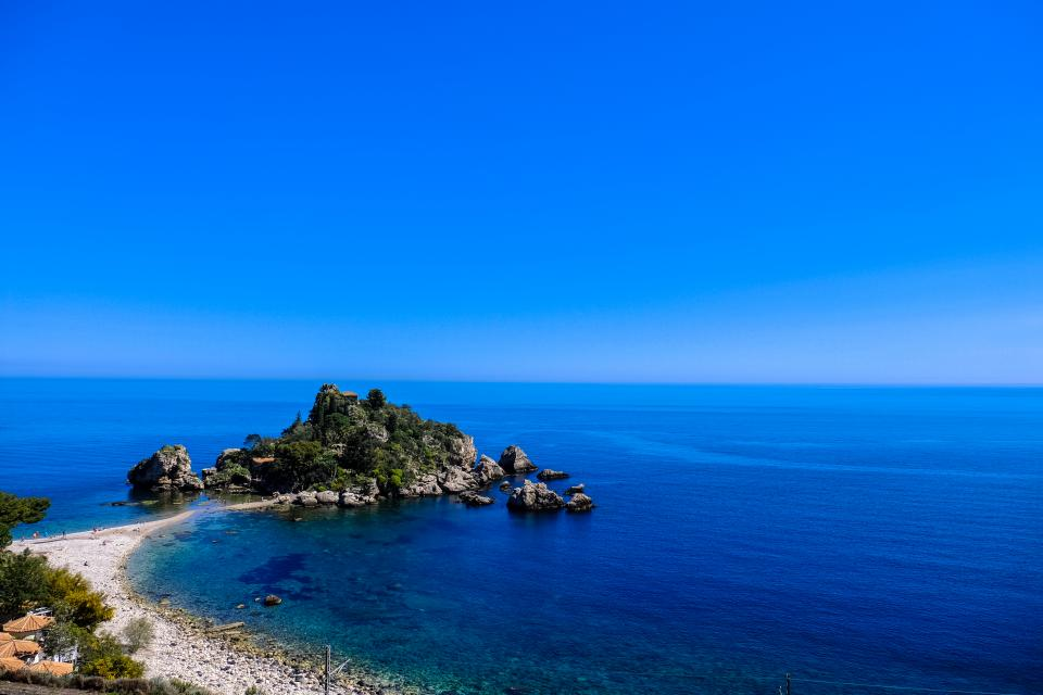 calm sea ocean blue water nature beach coast seashore rocks cliff island trees plants horizon sky landscape outdoor view travel