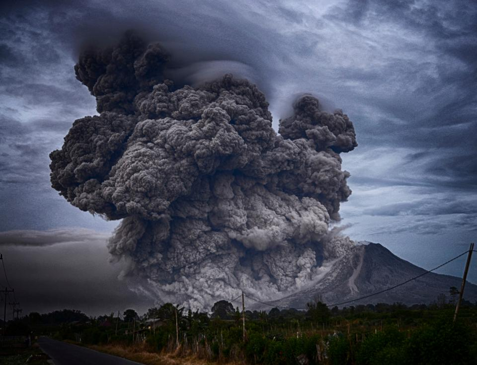 volcano explosion nature eruption smoke trees grass street road house transmission line sky clouds