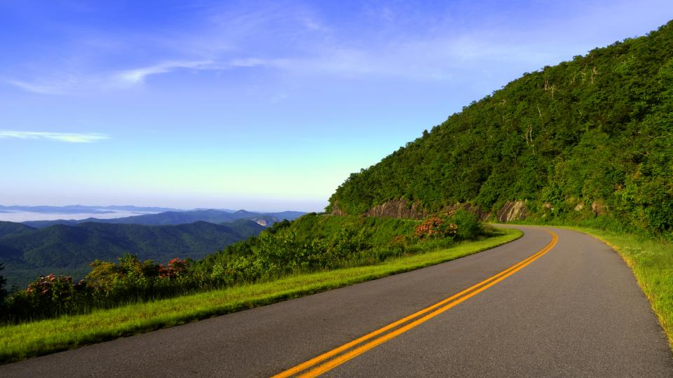 rural road highway pavement coast mountains hills green grass trees plants landscape blue sky nature