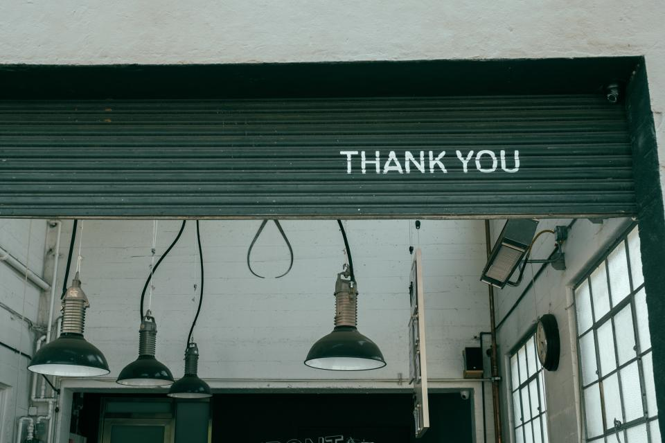 writings graffiti spray paint thank you lamps lights workshop studio overhead door whitewashed panels walls windows shop