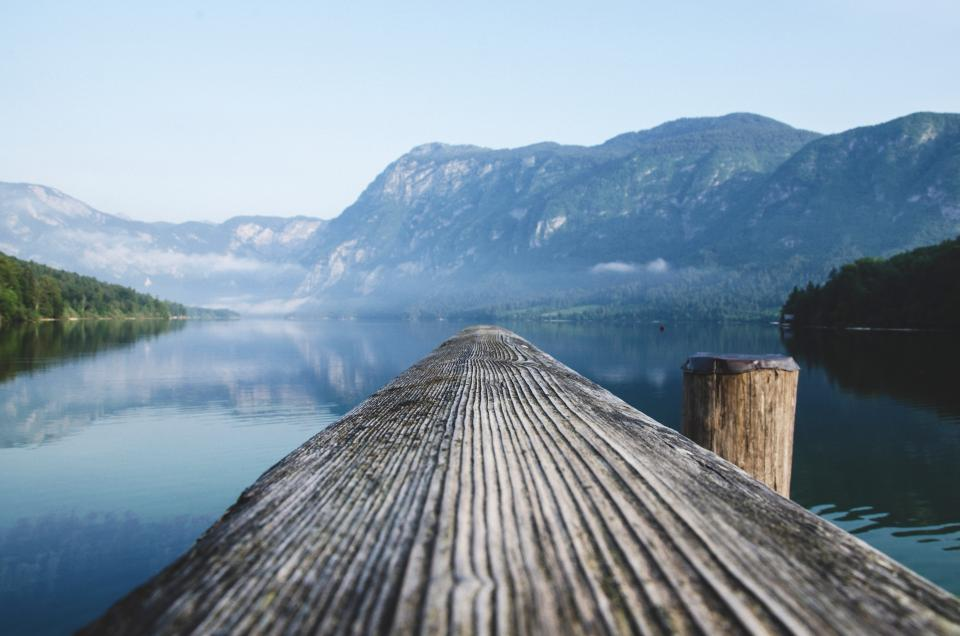 wood log lake water landscape nature mountains hills reflection sky outdoors dock
