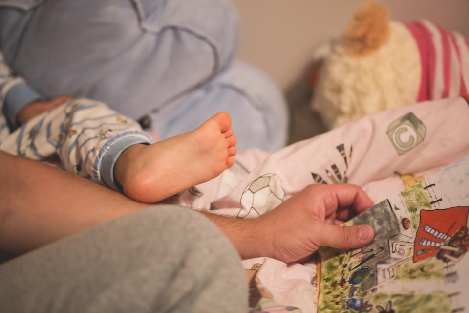child baby infant feet legs cute adorable bokeh flesh male father people story book time read bed sheets