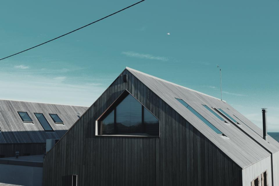 house roof wood panels windows sky clouds lines patterns minimalist blue brown