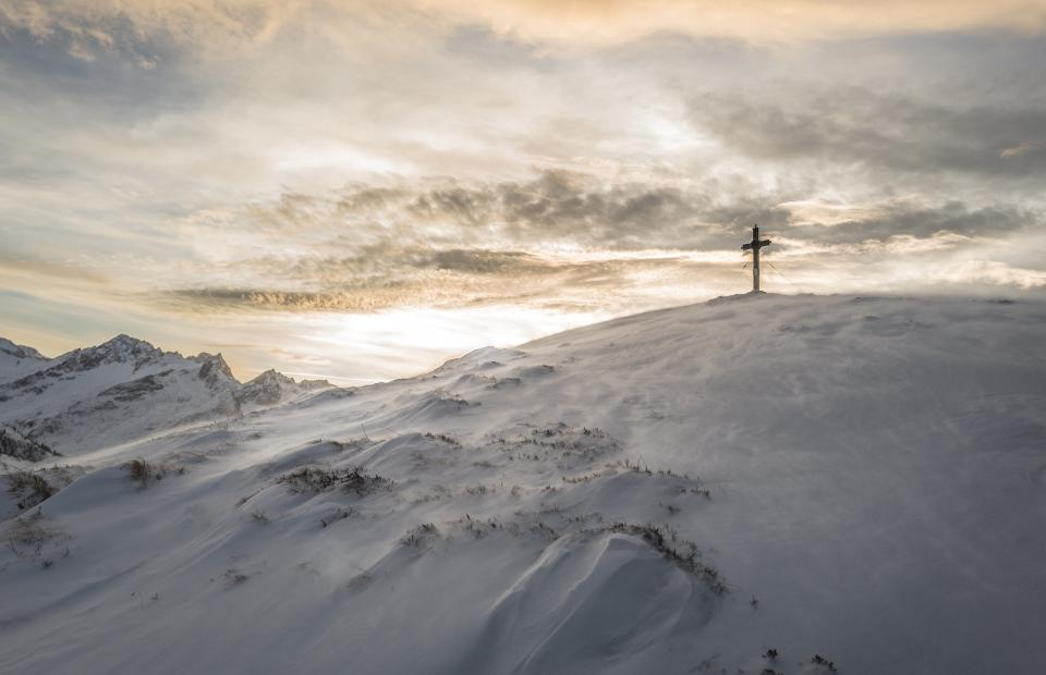 cross religion mountains hills snow winter sky clouds outdoors nature sunset